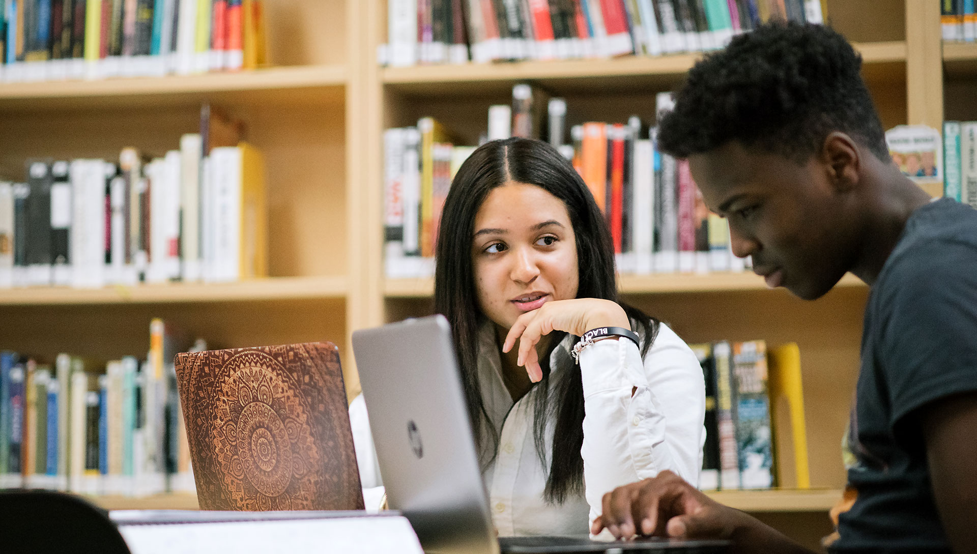 Two students working on laptops together in a library